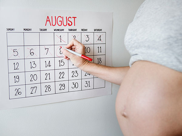 A pregnant woman circling dates on a calendar