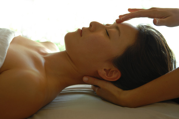 A woman getting her face and neck massaged